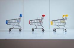 Miniboodschappenwagentje drie of supermarktkarretje leeg op lijst, Financiën en geld het winkelen concept Stock Foto