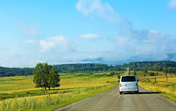 Minibus on the country highway. Against landscape Stock Photography