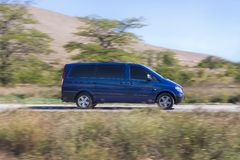 Minibus drives along the road against hilly background. Blurred background Royalty Free Stock Photography