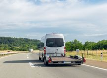 Minibus with empty tow truck transporter on highway. Space for text stock photography