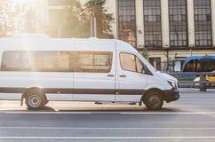 Minibus goes on the city street. White minibus goes on the city street Stock Photography