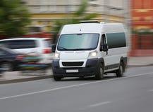 Minibus goes on the city street Royalty Free Stock Image