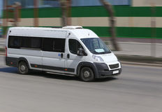 Minibus goes on the city street Royalty Free Stock Images
