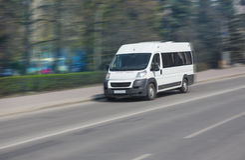 Minibus goes on the city street Stock Photo