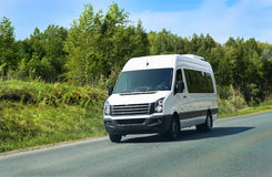 Minibus goes on the country highway. Along the wood Royalty Free Stock Photography