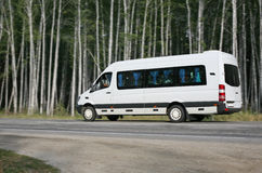 Minibus goes on the forest road. White minibus goes on the forest road Royalty Free Stock Photo