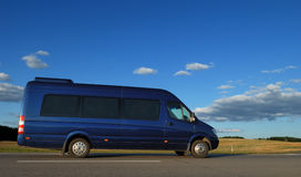 Minibus on highway. Blue minibus for transporting passengers on highway over blue sky Stock Image