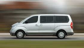 Minibus in motion. Fast moving white minibus on the road Stock Images