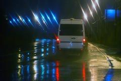 Minibus moves on the city street at night. White minibus moves on the city street at night Royalty Free Stock Photo