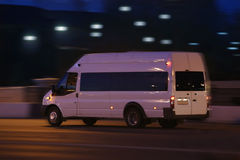 Minibus moves down the street at night Royalty Free Stock Photos