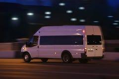 Minibus moves down the street at night. White minibus moves on the city street at night Royalty Free Stock Photos