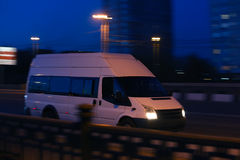 Minibus moves down the street at night Royalty Free Stock Photography