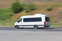 Minibus moves on the highway Stock Images