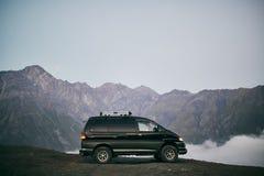 Minibusbergen op de achtergrond Bus voor vervoer van toeristen Zet Kazbegi op stock fotografie