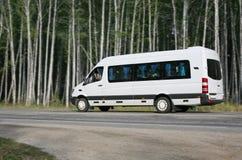 Minibusen går på skogvägen Royaltyfri Foto
