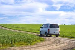 Minibuss på en grusväg mellan fält mot en blå himmel arkivbilder