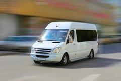 Minibussen går på stadsgatan Arkivbild