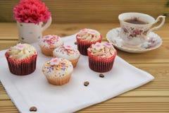 Minicakes met bevroren bloemdecoratie en een kop thee stock fotografie