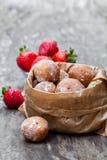 Minidiedoughnuts met aardbeijam worden gevuld in document zak op roest Stock Afbeeldingen