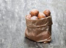 Minidoughnuts in document zak op rustieke houten lijst Stock Afbeelding