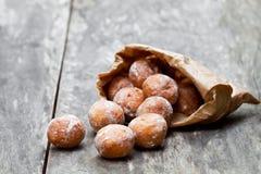 Minidoughnuts in document zak op rustieke houten lijst Stock Afbeeldingen