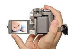 MiniDv camera in man hands. With baby image on display Royalty Free Stock Image