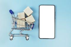 Minieinkaufswagen mit Pappschachteln Smartphone zu den Modellzwecken lokalisiert auf weißem Hintergrund stockfotografie