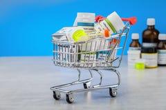 Minieinkaufswagen voll von homöopathischen Abhilfen auf blauem Hintergrund lizenzfreie stockbilder