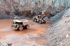 Miniera della cava della roccia del porfido scavatrice che carica un autocarro con cassone ribaltabile immagini stock