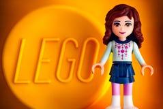 Minifigure девушки друзей Lego против желтой предпосылки с словом Стоковое Изображение