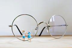 Minifigure begreppsrengöringsmedel i blått, rengörande exponeringsglas för hemmafru Royaltyfri Bild