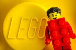 Minifigure de Lego Red Suit Brick Guy contra o fundo amarelo com palavra LEGO fotografia de stock royalty free