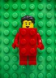 Minifigure de Lego Red Suit Brick Guy sur le fond vert de plaque de base Images libres de droits