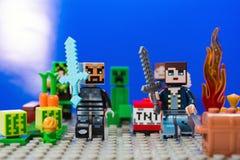 Minifigure-Eisenmann mit Diamantklinge und Charakteren des Spiel Minecraft-Laufs weg von der Kriechpflanze stockfoto