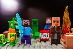 Minifigure Steve με το ξίφος διαμαντιών και χωρικός που οργανώνεται μακρυά από το αναρριχητικό φυτό Χαρακτήρες του παιχνιδιού Min στοκ εικόνα