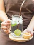 Minifruchtmarmeladentörtchen und -kalk gossen Detoxwasser hinein Lizenzfreies Stockbild
