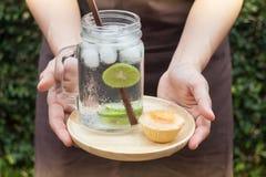 Minifruchtmarmeladentörtchen und -kalk gossen Detoxwasser hinein Stockbilder