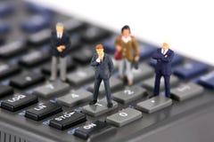 Minigeschäftsmänner auf Rechner Lizenzfreies Stockbild