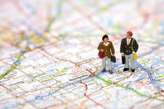 Minigeschäftsreisende auf einer Karte. Stockfotos