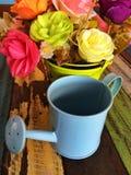 Minigießkanne verzieren auf Tabelle mit Blumen Lizenzfreie Stockbilder