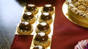Minigletsjer van de vrouwen de handen gezette chocolade op de lijst van de suikergoedbar stock videobeelden