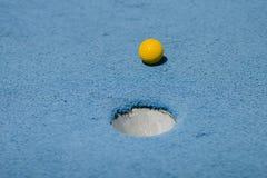 Minigolf-Ball-nähernde Loch-Nahaufnahme Lizenzfreie Stockbilder