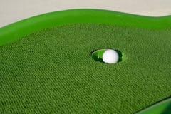 Minigolf boll i ett hål Arkivbild