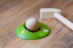 Minigolf-Holz für Kinder Golfclub und ein Ball während eines Minigolfspiels Kind-` s Spiele zu Hause Stockfotografie
