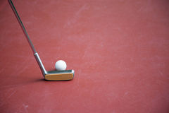 Minigolf iron racket with a white ball on a play ground. A minigolf iron racket with a white ball on a play ground with copyspace stock photo