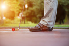 Minigolf player tries to put a ball into the hole at a sunny day Royalty Free Stock Images