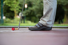Minigolf player tries to put a red ball into the hole at a sunny Royalty Free Stock Photography