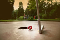 Minigolf player tries to put a small billard ball into the hole Royalty Free Stock Photos