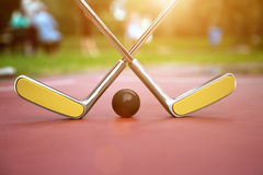 Minigolf scenery consist of two crossed minigolf rackets Royalty Free Stock Photo