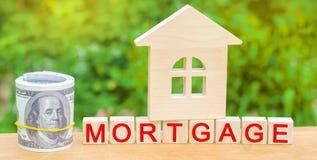 Minihaus- und Money Holzklötze und das Aufschrift ` Hypothek ` Kredit für Eigentum/Wohnung Betriebsmittelkredite für wirkliches lizenzfreie stockfotografie